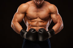 Ο μυϊκός νεαρός άνδρας με τον τέλειο κορμό με τα ABS έξι πακέτων, στα εγκιβωτίζοντας γάντια παρουσιάζει τις διαφορετικές μετακινή Στοκ Εικόνα