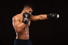 Ο μυϊκός νεαρός άνδρας με τον τέλειο κορμό με τα ABS έξι πακέτων, στα εγκιβωτίζοντας γάντια παρουσιάζει τις διαφορετικές μετακινή Στοκ εικόνες με δικαίωμα ελεύθερης χρήσης