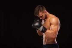 Ο μυϊκός νεαρός άνδρας με τον τέλειο κορμό με τα ABS έξι πακέτων, στα εγκιβωτίζοντας γάντια παρουσιάζει τις διαφορετικές μετακινή Στοκ εικόνα με δικαίωμα ελεύθερης χρήσης
