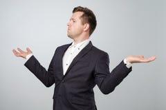 Ο μόνος-ικανοποιώντας και υπερήφανος καυκάσιος νεαρός άνδρας κοιτάζει κατά μέρος και διέδωσε τα χέρια του στοκ φωτογραφία