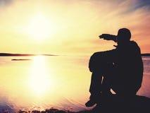Ο μόνος οδοιπόρος ατόμων κάθεται μόνο στην ακτή και απόλαυση του ηλιοβασιλέματος Άποψη πέρα από το δύσκολο απότομο βράχο στον ωκε Στοκ Εικόνες