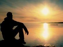 Ο μόνος οδοιπόρος ατόμων κάθεται μόνο στην ακτή και απόλαυση του ηλιοβασιλέματος Άποψη πέρα από το δύσκολο απότομο βράχο στον ωκε Στοκ Φωτογραφίες