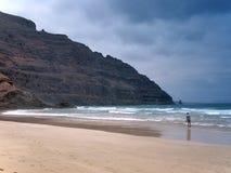 Ο μόνος φωτογράφος σε μια αμμώδη ωκεάνια παραλία πυροβολεί την κυματωγή κάτω από μια κλίση βράχου του ηφαιστείου Βαθύς σκούρο μπλ Στοκ Εικόνες
