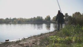 Ο μόνος ψαράς με τη μακριά γενειάδα περπατά στην όχθη ποταμού με την αλιεία των ράβδων Το άτομο εξετάζει την απόσταση, κάλυψη απόθεμα βίντεο
