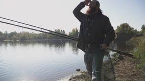 Ο μόνος ψαράς με τη μακριά γενειάδα περπατά στην όχθη ποταμού με την αλιεία των ράβδων κίνηση αργή απόθεμα βίντεο