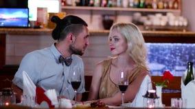 Ο νέοι άνδρας εραστών και η γυναίκα σε έναν καφέ κατά μια ρομαντική ημερομηνία, ευγενές φιλί, τα μάτια, μια όμορφη νέα γυναίκα, ρ φιλμ μικρού μήκους