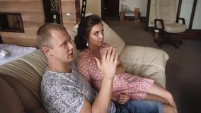 Ο νέοι ερωτευμένοι άνδρας και η γυναίκα ζευγών βρίσκονται στον καναπέ και τη TV προσοχής απόθεμα βίντεο