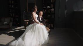 Ο νέοι ερωτευμένοι άνδρας και η γυναίκα ζευγών σε έναν γάμο ντύνουν στο εσωτερικό φιλμ μικρού μήκους