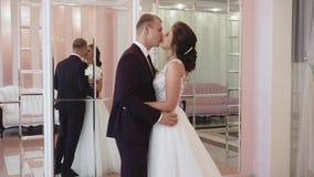 Ο νέοι ερωτευμένοι άνδρας και η γυναίκα ζευγών σε έναν γάμο ντύνουν στο εσωτερικό απόθεμα βίντεο