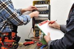 Ο νέοι ηλεκτρολόγος και ο μηχανικός τεχνικών ελέγχουν την τάση του α Στοκ Φωτογραφίες