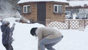 Ο νέοι πατέρας και ο γιος ρίχνουν τις χιονιές ο ένας στον άλλο απόλαυση του οικογεν&epsil απόθεμα βίντεο