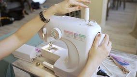 Ο νέοι σχεδιαστής ιματισμού και seamstress η γυναίκα εργάζονται με την κινηματογράφηση σε πρώτο πλάνο ράβοντας μηχανών στο στούντ απόθεμα βίντεο