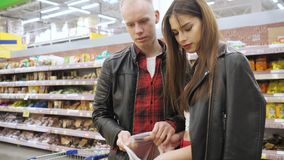 """Ο νέοι τύπος και Ï""""Î¿ κορίτσι ζευγών αγοράζουν friuts σε μια υπεραγορά απόθεμα βίντεο"""