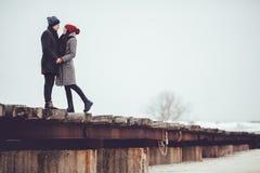 Ο νέοι τύπος και το κορίτσι στη χειμερινή ένδυση, αγκαλιάζουν και απολαμβάνουν το τοπίο του χειμώνα στοκ φωτογραφία με δικαίωμα ελεύθερης χρήσης