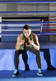 Ο νέος αθλητής κάθεται στην άκρη του δαχτυλιδιού με την πράσινη πετσέτα στοκ φωτογραφία