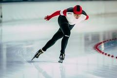 Ο νέος αθλητής γυναικών κινηματογραφήσεων σε πρώτο πλάνο speedskater πηγαίνει γύρω από τη στροφή της αίθουσας παγοδρομίας Στοκ φωτογραφία με δικαίωμα ελεύθερης χρήσης