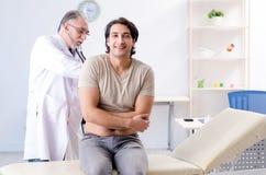 Ο νέος αρσενικός ασθενής που επισκέπτεται τον παλαιό γιατρό στοκ φωτογραφίες