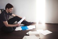 Ο νέος αρσενικός επιχειρηματίας κάνει τη συνεδρίαση 'brainstorming' στο πάτωμα στο διαμέρισμα Δημιουργική προσέγγιση στην επιχείρ Στοκ εικόνα με δικαίωμα ελεύθερης χρήσης