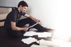 Ο νέος αρσενικός επιχειρηματίας κάνει τη συνεδρίαση 'brainstorming' στο πάτωμα στο διαμέρισμα Δημιουργική προσέγγιση στην επιχείρ Στοκ Φωτογραφία
