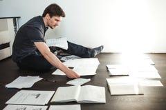 Ο νέος αρσενικός επιχειρηματίας κάνει τη συνεδρίαση 'brainstorming' στο πάτωμα στο διαμέρισμα Δημιουργική προσέγγιση στην επιχείρ Στοκ Φωτογραφίες