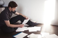 Ο νέος αρσενικός επιχειρηματίας κάνει τη συνεδρίαση 'brainstorming' στο πάτωμα στο διαμέρισμα Δημιουργική προσέγγιση στην επιχείρ Στοκ φωτογραφίες με δικαίωμα ελεύθερης χρήσης