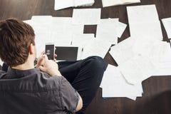 Ο νέος αρσενικός επιχειρηματίας κάνει τη συνεδρίαση 'brainstorming' στο πάτωμα στο διαμέρισμα Δημιουργική προσέγγιση στην επιχείρ Στοκ φωτογραφία με δικαίωμα ελεύθερης χρήσης