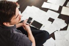 Ο νέος αρσενικός επιχειρηματίας κάνει τη συνεδρίαση 'brainstorming' στο πάτωμα στο διαμέρισμα Δημιουργική προσέγγιση στην επιχείρ Στοκ Εικόνα
