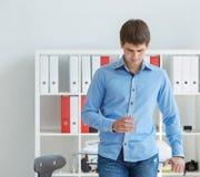 Ο νέος αρσενικός επιχειρηματίας κοιτάζει κάτω από το γυαλί εκμετάλλευσης με το νερό διαθέσιμο Στοκ φωτογραφία με δικαίωμα ελεύθερης χρήσης