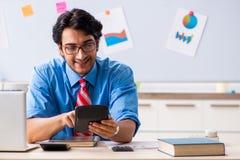 Ο νέος αρσενικός οικονομικός διευθυντής που εργάζεται στο γραφείο στοκ εικόνα με δικαίωμα ελεύθερης χρήσης