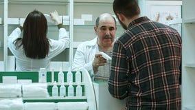 Ο νέος αρσενικός πελάτης αγοράζει τα ιατρικά προϊόντα σε ένα φαρμακείο Στοκ Φωτογραφίες