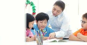 Ο νέος ασιατικός δάσκαλος βοηθά τα νέα σχολικά παιδιά στην κατηγορία, απόθεμα βίντεο