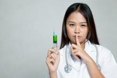 Ο νέος ασιατικός θηλυκός γιατρός με τη σύριγγα παρουσιάζει ήρεμο σημάδι Στοκ Εικόνες