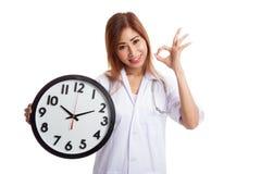 Ο νέος ασιατικός θηλυκός γιατρός παρουσιάζει ΕΝΤΆΞΕΙ με ένα ρολόι Στοκ Φωτογραφίες