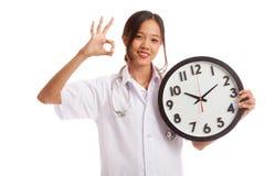 Ο νέος ασιατικός θηλυκός γιατρός παρουσιάζει ΕΝΤΆΞΕΙ με ένα ρολόι Στοκ φωτογραφίες με δικαίωμα ελεύθερης χρήσης