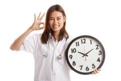 Ο νέος ασιατικός θηλυκός γιατρός παρουσιάζει ΕΝΤΆΞΕΙ με ένα ρολόι Στοκ εικόνα με δικαίωμα ελεύθερης χρήσης