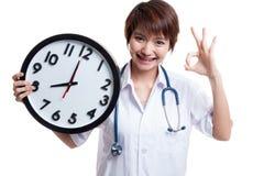 Ο νέος ασιατικός θηλυκός γιατρός παρουσιάζει ΕΝΤΆΞΕΙ με ένα ρολόι Στοκ φωτογραφία με δικαίωμα ελεύθερης χρήσης