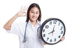 Ο νέος ασιατικός θηλυκός γιατρός παρουσιάζει ΕΝΤΆΞΕΙ με ένα ρολόι Στοκ Εικόνες
