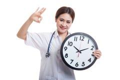 Ο νέος ασιατικός θηλυκός γιατρός παρουσιάζει ΕΝΤΆΞΕΙ με ένα ρολόι Στοκ Εικόνα
