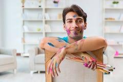Ο νέος αστείος καλλιτέχνης που εργάζεται στη νέα ζωγραφική στο στούντιό του στοκ φωτογραφίες