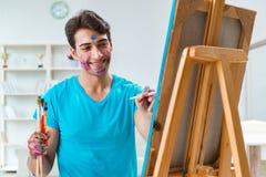 Ο νέος αστείος καλλιτέχνης που εργάζεται στη νέα ζωγραφική στο στούντιό του στοκ φωτογραφία με δικαίωμα ελεύθερης χρήσης