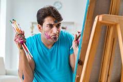 Ο νέος αστείος καλλιτέχνης που εργάζεται στη νέα ζωγραφική στο στούντιό του Στοκ Εικόνες