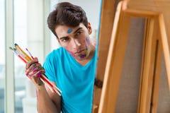 Ο νέος αστείος καλλιτέχνης που εργάζεται στη νέα ζωγραφική στο στούντιό του στοκ φωτογραφίες με δικαίωμα ελεύθερης χρήσης