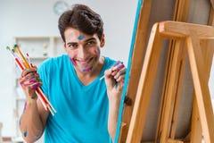 Ο νέος αστείος καλλιτέχνης που εργάζεται στη νέα ζωγραφική στο στούντιό του στοκ εικόνα με δικαίωμα ελεύθερης χρήσης