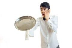 Ο νέος αστείος σερβιτόρος ρίχνει έναν δίσκο στο πάτωμα και κράτησε τη σφαίρα για το πρόσωπο στοκ εικόνα