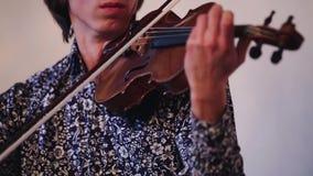 Ο νέος βιολιστής στο μπλε πουκάμισο σχεδίων αποδίδει στον εορτασμό μουσικός Απόδοση απόθεμα βίντεο