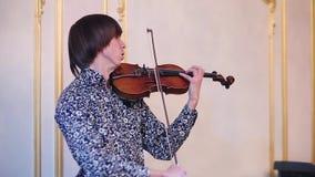 Ο νέος βιολιστής στο μπλε πουκάμισο σχεδίων αποδίδει στο γεγονός στην ιστορική αίθουσα μουσικός Απόδοση φιλμ μικρού μήκους