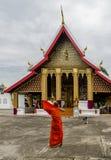 Ο νέος βουδιστικός μοναχός ρυθμίζει το πορτοκαλί ράσο του στο ναό Wat Mahathat σε Luang Prabang, Λάος στοκ φωτογραφίες