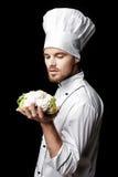 Ο νέος γενειοφόρος αρχιμάγειρας ατόμων άσπρο σε ομοιόμορφο κρατά το φρέσκο κουνουπίδι στο μαύρο υπόβαθρο Στοκ Εικόνες