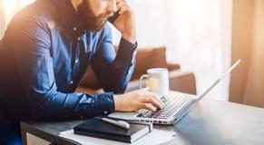 Ο νέος γενειοφόρος επιχειρηματίας κάθεται στον πίνακα, που λειτουργεί στον υπολογιστή, που μιλά στο τηλέφωνο κυττάρων Στο σημειωμ Στοκ φωτογραφία με δικαίωμα ελεύθερης χρήσης