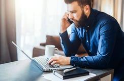 Ο νέος γενειοφόρος επιχειρηματίας κάθεται στον πίνακα, που λειτουργεί στον υπολογιστή, που μιλά στο τηλέφωνο κυττάρων Στο σημειωμ Στοκ φωτογραφίες με δικαίωμα ελεύθερης χρήσης